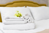 Stack of towels with flower decor in a hotel room - 184515930