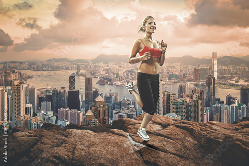 Foto op Canvas Jogging slim blonde girl jogging up to the rocks hill over the metropolis
