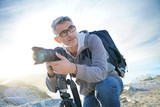 Portrait of photographer taking pictures in natural landscape - 184530348