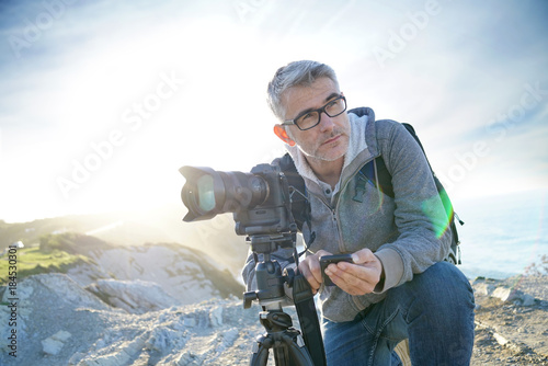 Photographer using wifi device to look at photo shots
