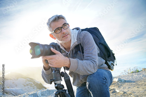 Foto op Canvas Wit Portrait of photographer taking pictures in natural landscape