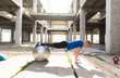 Young handsome athlete man doing pushups with silver pilates ball  in an old abandoned building outdoor