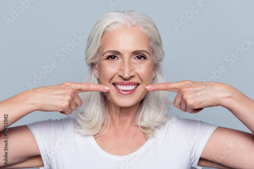 Leinwandbild Motiv Concept of having strong healthy straight white teeth at old age. Close up portrait of happy with beaming smile female pensioner pointing on her perfect clear white teeth, isolated on gray background