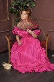 medieval lady in a pink dress with a fan - 184534332
