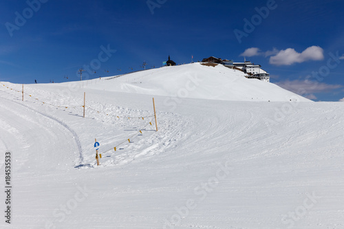 Foto op Aluminium Nachtblauw View to number 8 beginners blue ski slope at SCHMITTENHOHEBAHN 2000 meters peak with Elisabethkapelle on the top at Zell Am See Austria Alps mountain Schmitten resort
