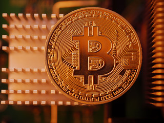 Golden bitcoin BTC coin on cooling hardware background, macro closeup. Blockchain investment technology concept.