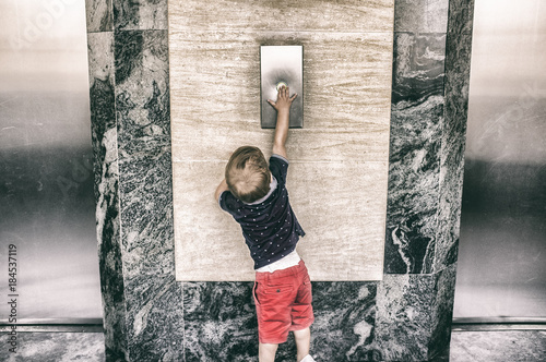 Poster Toddler boy calling elevator button
