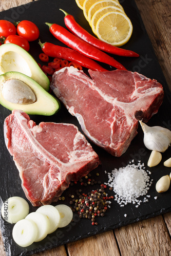 Plexiglas Steakhouse Raw t-bone steak with vegetables and spices close-up. vertical