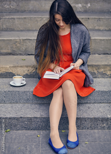 Sticker Young attractive student in red dress studying and reading a book.