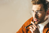 portrait of fashionable pensive man smoking cigar and looking away isolated on beige - 184549712