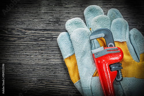 Plumbing pipe wrench protective gloves on wooden board