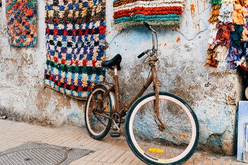 rusty bicycle standing at wall of marrakech souk