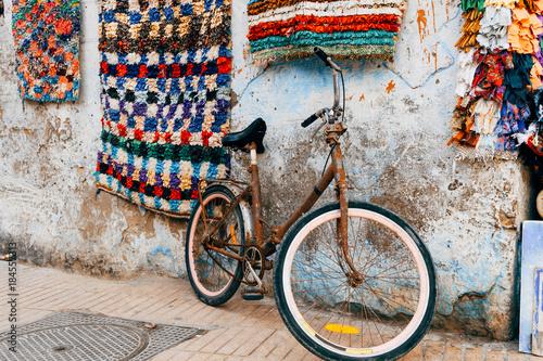 zardzewiały rower stojący na ścianie suku marrakeszu
