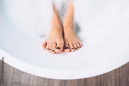 Well groomed woman's legs in bath foam close up image - 184565993