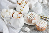 Cups with cacao and marshmallow, cupcakes and different decorations - 184583386