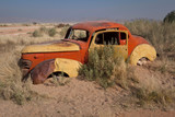 Rusting car submerged in sand - 184592101
