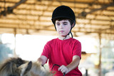 A little boy riding a horse. First lessons of horseback riding - 184604711
