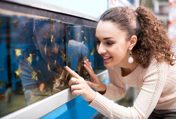 Positive young woman selecting aquarium fish
