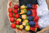 skewers of fresh  fruit and coconut for sale on the beach