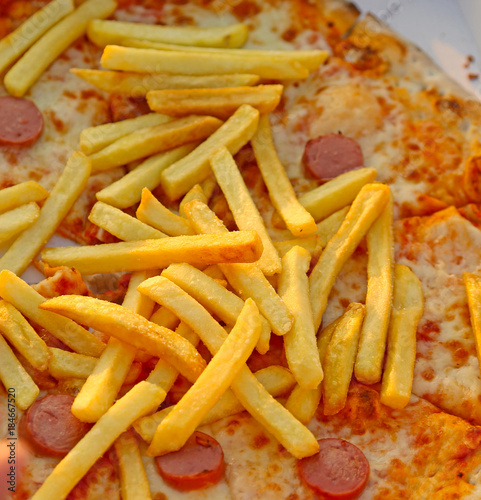 Poster Pizzeria fries over the tasty pizza with wurstel mozzarella and tomato