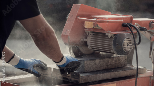 Retro image of building contractor cutting through a paving stone