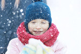 child  playing in the snow / the girl in warm sports clothes is playing with snow on a winter walk. Warm woolen hat, down jacket. Concept of a happy baby walk. - 184676116