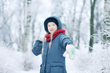child  playing in the snow / the girl in warm sports clothes is playing with snow on a winter walk. Warm woolen hat, down jacket. Concept of a happy baby walk. - 184676117