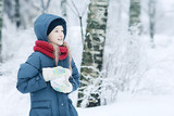 smiling happy child in winter / healthy cheerful girl in warm clothes at a frosty winter walk. Snow portrait of a child. Concept of health, happiness, family - 184676119