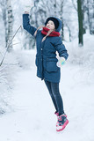 child  playing in the snow / the girl in warm sports clothes is playing with snow on a winter walk. Warm woolen hat, down jacket. Concept of a happy baby walk. - 184676128