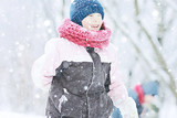 child  playing in the snow / the girl in warm sports clothes is playing with snow on a winter walk. Warm woolen hat, down jacket. Concept of a happy baby walk. - 184676145