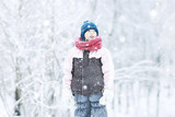 child  playing in the snow / the girl in warm sports clothes is playing with snow on a winter walk. Warm woolen hat, down jacket. Concept of a happy baby walk. - 184676159