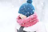 child  playing in the snow / the girl in warm sports clothes is playing with snow on a winter walk. Warm woolen hat, down jacket. Concept of a happy baby walk. - 184676164