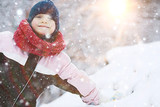 child  playing in the snow / the girl in warm sports clothes is playing with snow on a winter walk. Warm woolen hat, down jacket. Concept of a happy baby walk. - 184676169