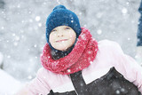 child  playing in the snow / the girl in warm sports clothes is playing with snow on a winter walk. Warm woolen hat, down jacket. Concept of a happy baby walk. - 184676170