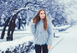 Winter portrait of young beautiful brunette woman wearing fur coat.