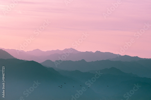 Fotobehang Groen blauw Mountain range at sunrise light