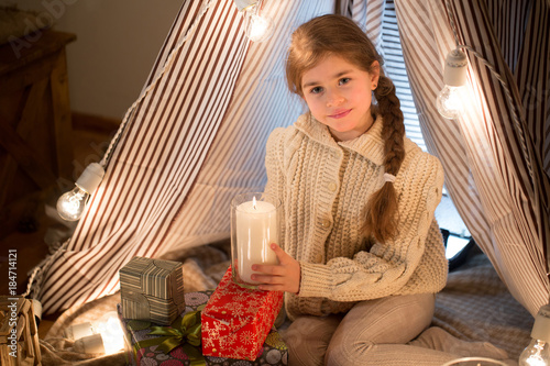 Beautiful little girl sitting with a burning candle in his hands Poster