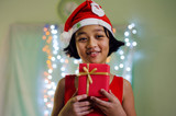 Kids in Red Dress Hold a Christmas Gift Box with Defocused Background on the Christmas Time.