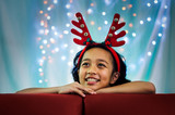 Asian Kids Wearing a Reindeer Headband and Smiling with Defocused Background.