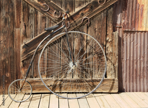 Aluminium Fiets Old High Wheel Bicycle in Front of Whethered Barn Door