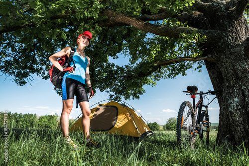 Young lady stands on a meadow with green grass under tree and set up a tent