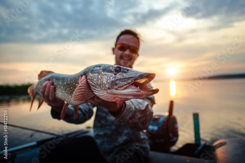 Happy angler holds pike fish sitting in a boat with river on the background