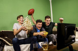 Ecstatic family, father and sons cheering for touchdown, while watching american football, funny  - 184725134