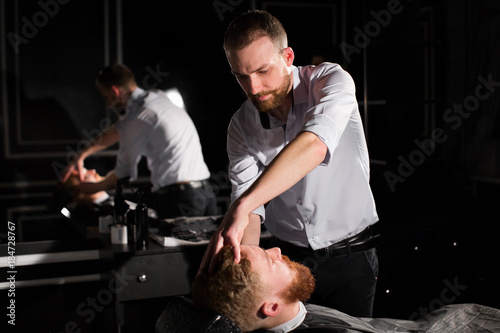 Hairdresser is shaving male beard with the knife. Handsome bearded man is getting shaved by hairdresser at the barbershop © Artem