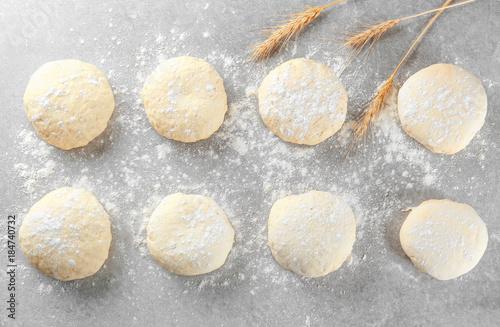 Raw dough balls with flour on table