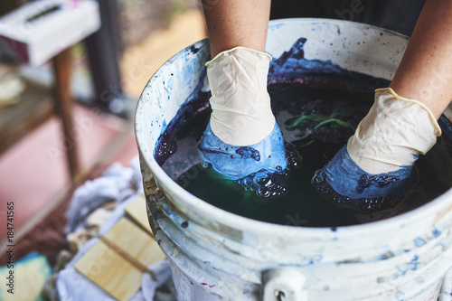 a woman dying fabric with indigo dye.