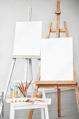 Vertical light shot of painter workplace mock up. Watercolor, brushes and accessories. Two wooden easels with blank painting canvas as copy space for mock up isolated on artistic studio background.
