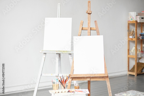 Horizontal light shot of painter workplace mock up. Watercolor, brushes and accessories. Two wooden easels with blank painting canvas as copy space for mock up isolated on artistic studio background.