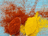two heaping scoops of spices of paprika powder and turmeric, curry, powder scattered on the wooden blue bright light color table - 184788185