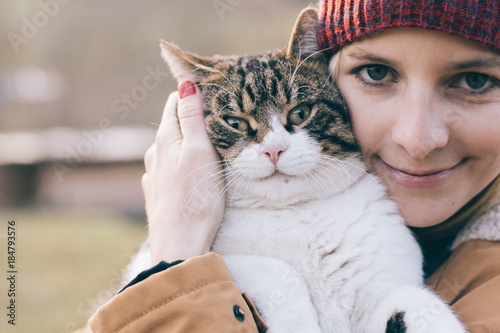 Woman and her cat playing outdoor - 184793576